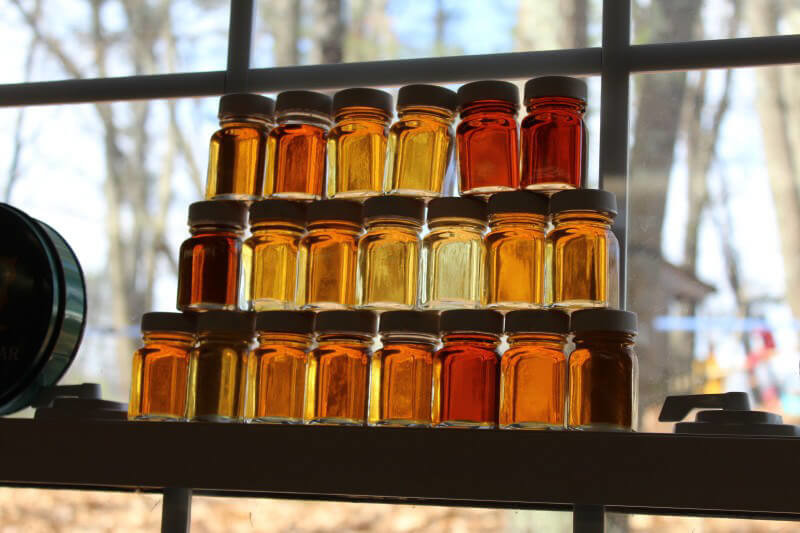Glass jars filled with golden maple syrup