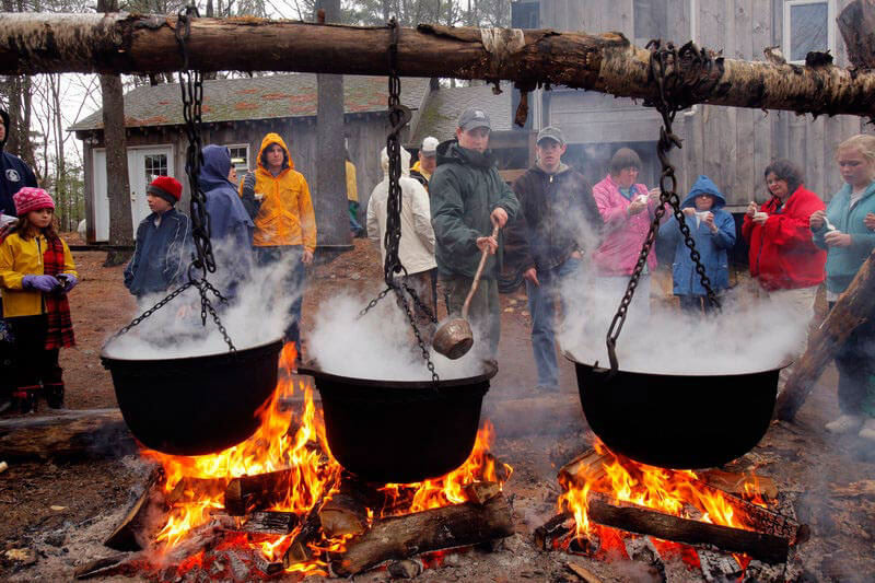 black cauldrons of sap boiling over an orange fflame