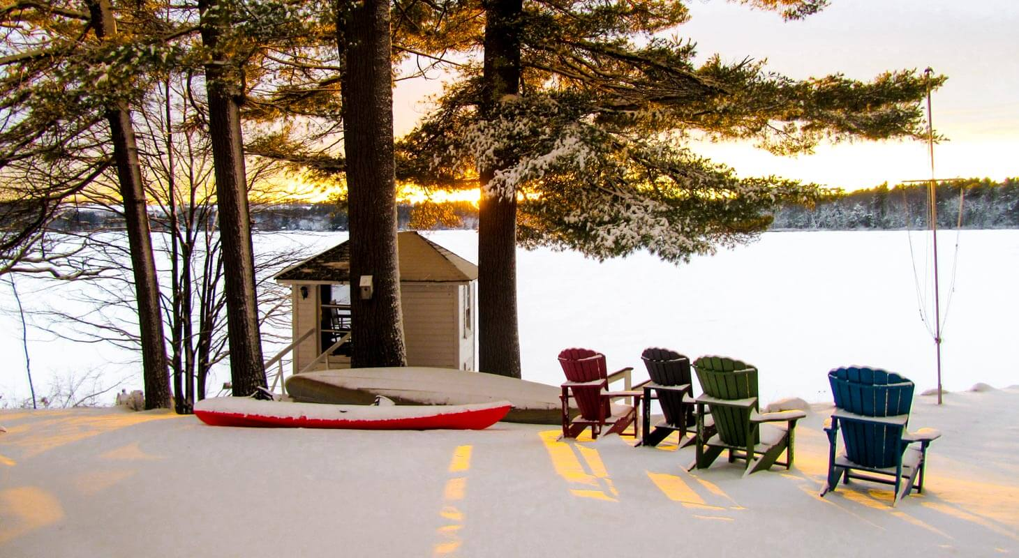 Winter sunset over a snowy frozen lake landscape with Adirondack chairs in the foreground during a romantic winter getaway