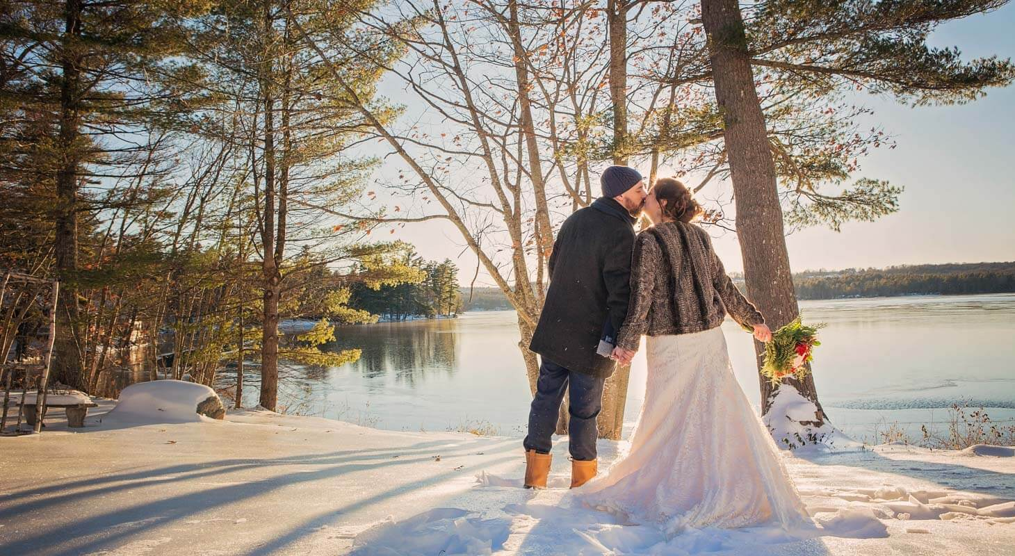 Bride and groom together overlooking snowy lake at sunset.
