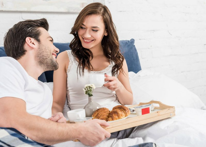 Young couple enjoying breakfast in bed