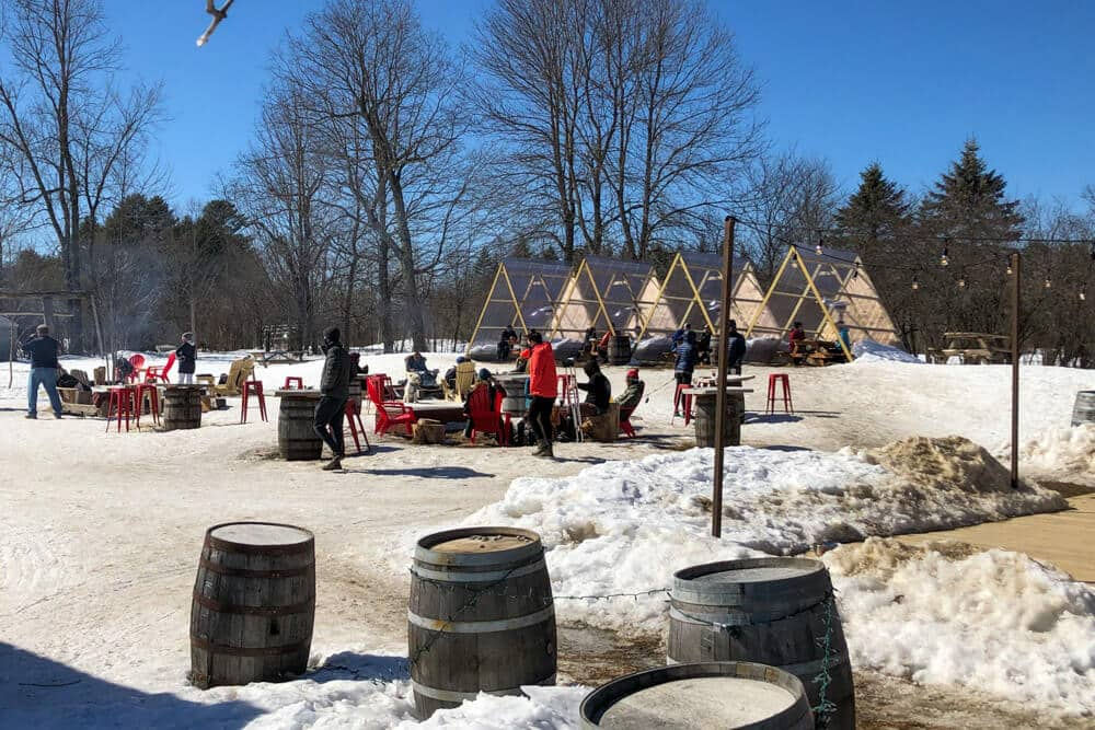 People around fire pit with snow on ground at Oxbow Beer Garden