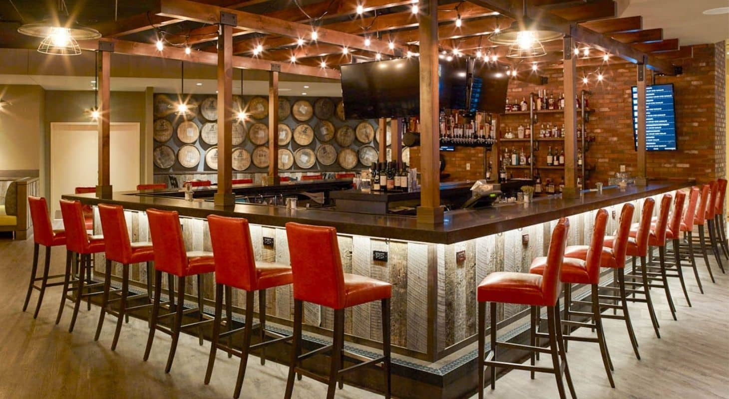 Oxford Casino bar with red bar stools and shelves of bottles