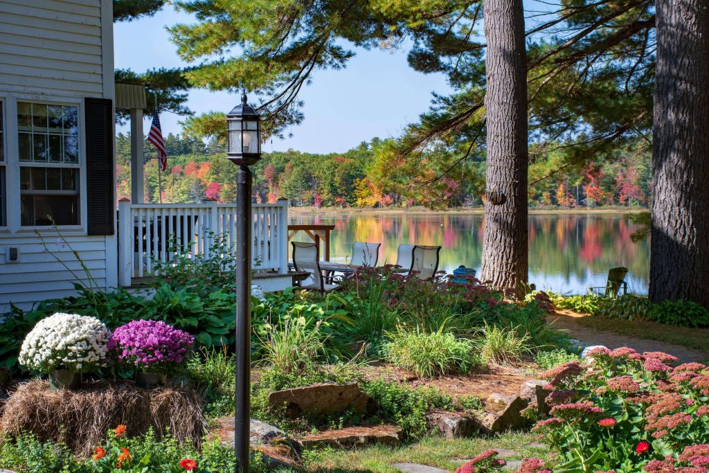 View of the Inn's fall flowers and foliage across the lake