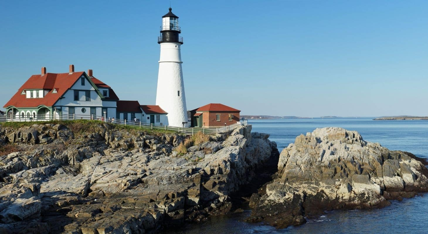 White lighthouse with red roof surrounded by rocks and crystal blue waters and skies