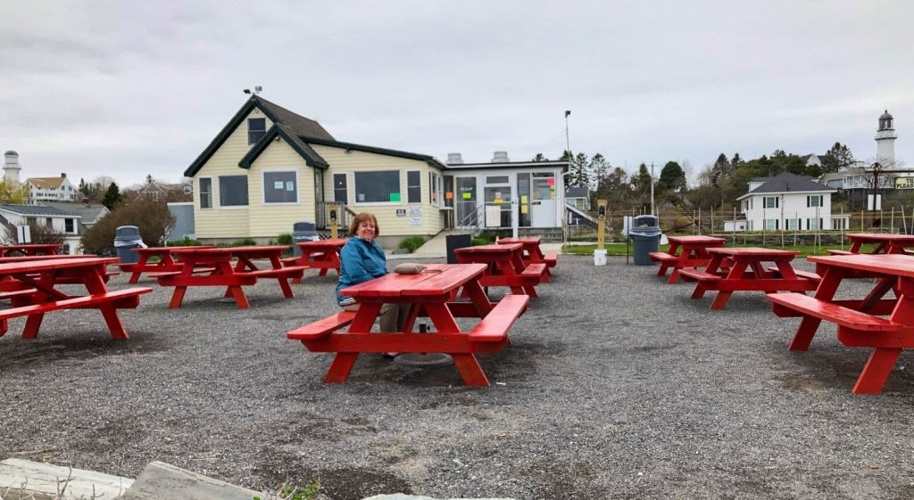 Sue sitting at a red picnic table at the Lobster Shack at two lights