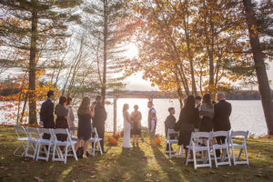Intimate lakeside wedding under arbor and foliage in Maine