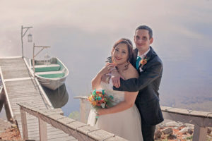 Couple embracing on stairs to dock at a lakeside elopement