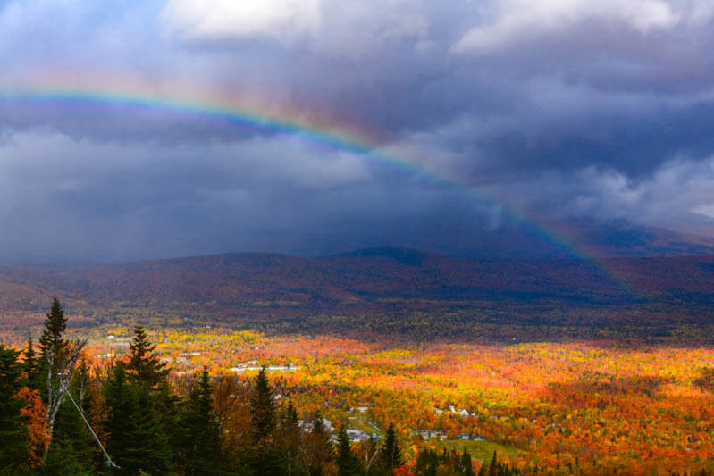 Rainbow over fall foliage covered valley in Maine