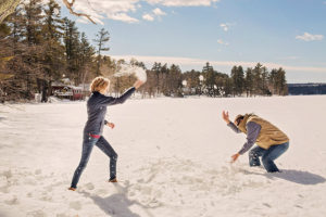 Winter elopement snowball fight on the lake