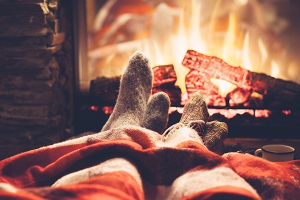 couple's feet by the fire in socks