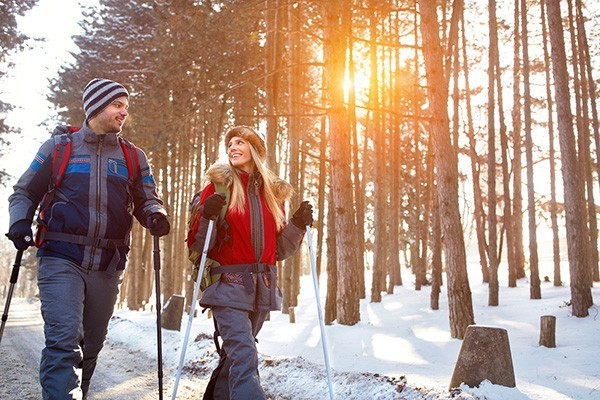 couple hiking in the woods in the snow