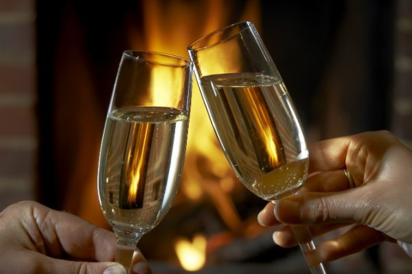 Wedding champagne toast in front of a fire