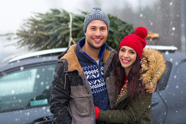 Couple in the snow with a Christmas tree on their car