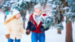Couple in coats and hats walking through snowy trees
